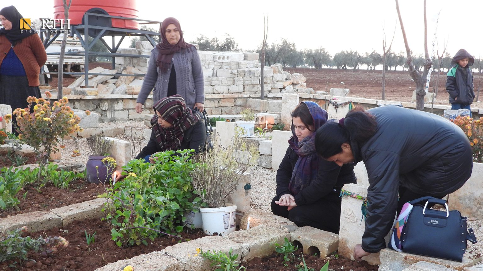 Displaced Yezidi women light candles on the graves of their loved ones in Ahras, Syria (North Press)